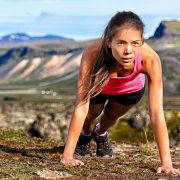 Fitness push-ups woman doing pushups outdoors in nature