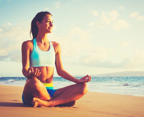 Happy young woman practicing yoga on the beach at sunset.