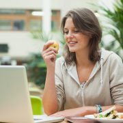 Young woman using laptop while eating apple