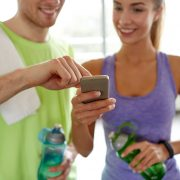 close up of smiling young woman and personal trainer